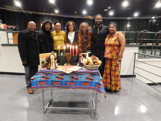Faculty and invited guest accompanied by the Kwanzaa table.