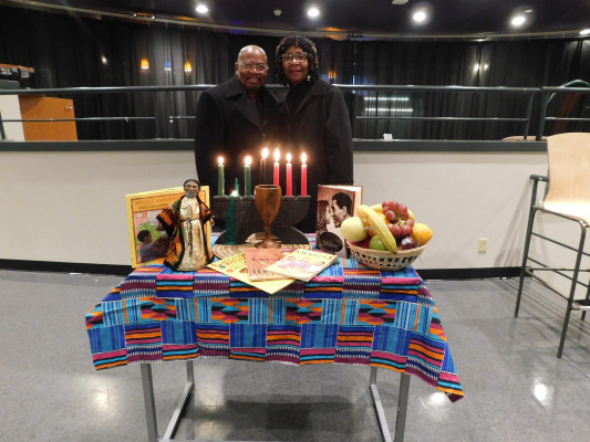 Invited guest, Mayor Aidsand of Collegeville and his wife, accompanied by the Kwanzaa table.