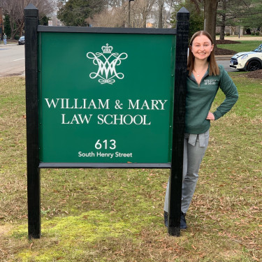 Corinne Cichowicz standing next to a sign for William and Mary Law School