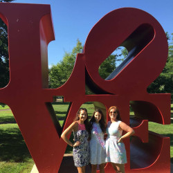 Students posing in front of Urisinus Love statue