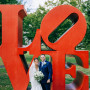 Alumni Couple standing in front of Love sign