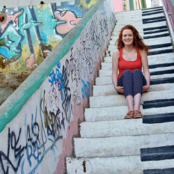 Monica Reuman sitting on a colorful stairway
