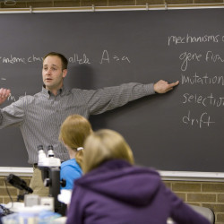 Photo of Cory Straub teaching in front of a chalkboard