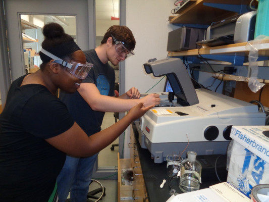 Chase and Nerica insert a sample of antibiotics attached to carbon nanotubes into the infrared spectrometer