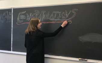 Student writing a farewell to the seniors on a chalkboard.