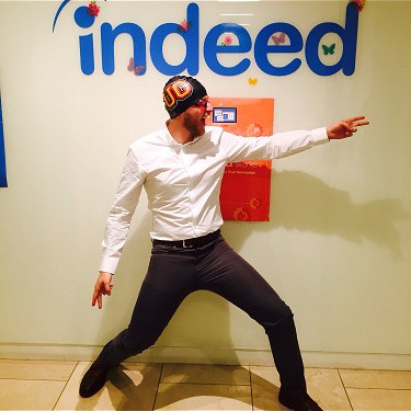 "James Marrone posing in front of an ""Indeed"" logo"