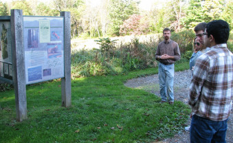 Examining the interpretive signage at the trailhead.