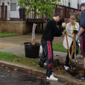 ENV Alum Matt Chorney (right with poledigger) plants trees in Camden, NJ.