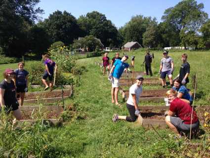 Students help prepare community gardening plots for a new season of planting.