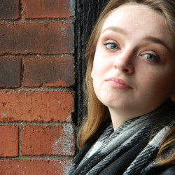 Shannon Byrne posing in front of a brick wall