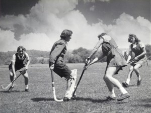 Four Students playing field hockey in the 1950s.