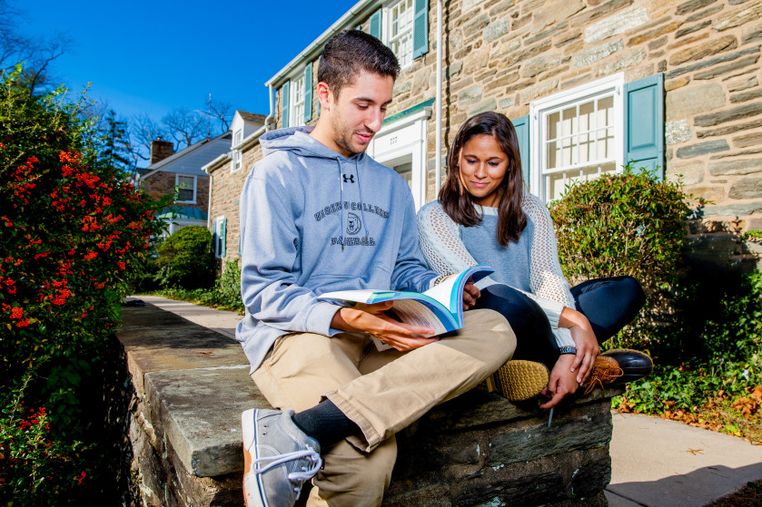 Male and female student studying outdoors