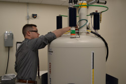 Prof. Ryan Walvoord demonstrates the Nuclear Magnetic Resonance spectrometer.