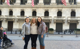 CIE Fellow Riley Acton '15 with Sydney Eckert and Kelly McLaughlin, both '18, in front of the New York Stock Exchange
