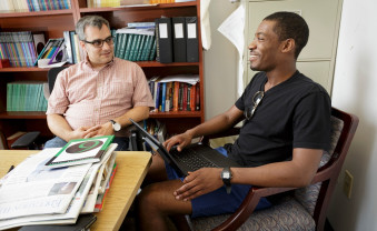 Seamus Mulryan, an assistant professor of education, consults with Sam Pope '19.