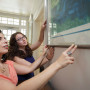 Professor Deborah Barkun (left) and Olivia Schultz look at artwork on display at Hillel House.