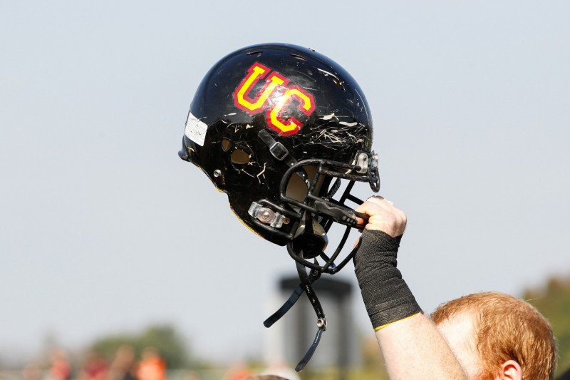 Ursinus College football helmet being lifted in the air