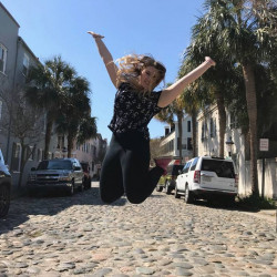 Photo of Lizzy DeWitt jumping in the streets of the city