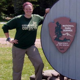 Allie Cook standing next to a National Park Service sign