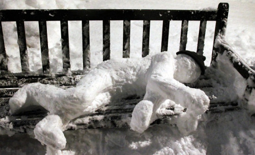 Snowman laying on bench