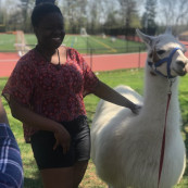 Photo of Sianneh Vesslee petting a llama